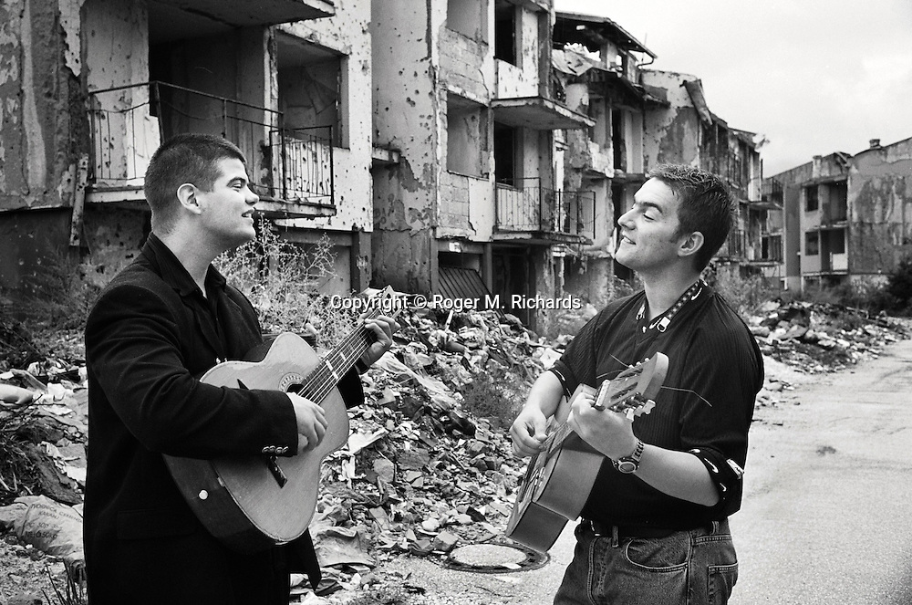 Alan Trtic, left, and his friend Sasha Prajzler play their guitars in a portrait amid the ruins of a section of the Sarajevo suburb of Dobrinja, which was virtually cut off from the rest of government-controlled Sarajevo during the Bosnian Serb siege of the city. Residents of Dobrinja suffered terribly in the siege, and people even resorted to burying their dead in their backyards and gardens as to get casualties into the city was incredibly dangerous. PHOTO BY Roger Richards/DVreporter.com