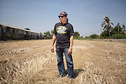 April 2013 - Mr. Kritsada Rotcharach standing in the wheat field behind his village in Sai Noi. He was one of the six men who volunteered to be left behind and monitor the situation while the rest of the people were given order to evacuate the area. For days he was confined in the top floor of his town-house, having to climb down a mango tree to get to his boat.<br /> The whole neighbourhood was ready to face the flood with pumps and sand bags but they were not expecting the water to come from the fields behind their houses. © Giorgio Taraschi for The Rockefeller Foundation/Next City