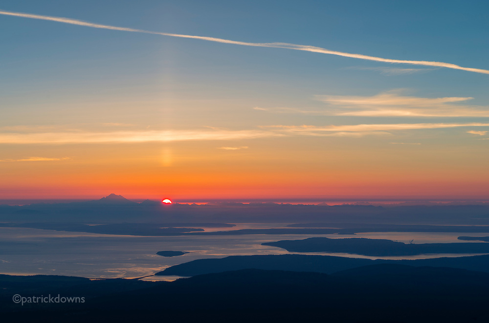 The sunrise peeks over the Cascades and Mt. Baker, seen from Deer Park ridge in Olympic National Park. Whidbey Island, Discovery Bay, Protection Island and Port Townsend can be seen.