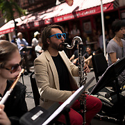 """June 21, 2014 - New York, NY : <br /> The city was flooded with music on Saturday as Make Music New York brought more than 1,300 free concerts to the city's streets and parks. The annual festival's program included the performance """"'In (Key)' - New Compositions in Celebration of Terry Riley's 'In C' @ 50 Years"""" on Cornelia Street, in front of the Cornelia Street Cafe in Greenwich Village, on Saturday afternoon. The musicians including Gina Izzo, foreground left on flute, and Vasko Dukovski, center on bass clarinet, performed in the street in front of the Cornelia Street Cafe.  <br /> CREDIT: Karsten Moran for The New York Times"""