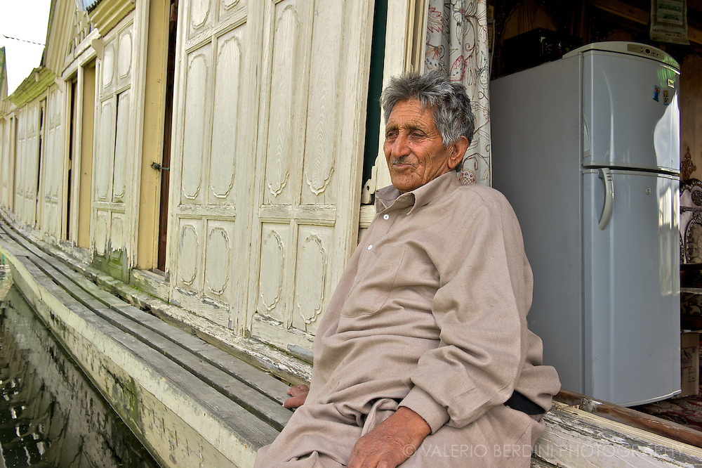 Old man in front of his big houseboat equipped with a brand new modern fridge. Dal Lake Srinagar, Kashmir. India