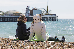 April 14, 2018 - Brighton, East Sussex, United Kingdom - Brighton, UK. Members of the public dress up in winter coats with hats and scarfs to spent some time on the beach in Brighton and Hove at the start of the Easter Bank holiday weekend. (Credit Image: © Hugo Michiels/London News Pictures via ZUMA Wire)