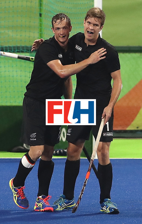 RIO DE JANEIRO, BRAZIL - AUGUST 14:  Hugo Inglis  (L) of New Zealand celebrates with team mate James Coughlan after scoring the first goal during the Men's hockey quarter final match between the Germany and New Zealand on Day 9 of the Rio 2016 Olympic Games at the Olympic Hockey Centre on August 14, 2016 in Rio de Janeiro, Brazil.  (Photo by David Rogers/Getty Images)
