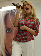 Pop star Jessica Simpson performs in front of a large likeness at a shopping mall in Brandon, Florida, as part of a promotional tour for Tommy Jeans.