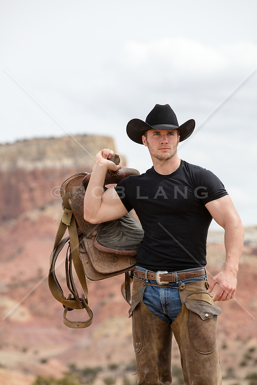 hot cowboy holding a saddle outdoors