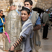 Israel, Jerusalem, Jewish teenage boy carries torah scrolls before start of his Bar Mitzvah celebration at Western Wall