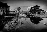 Ishinomaki, still flooded, on the one year anniversary of the 11 March 2011 Great East Japan Earthquake and Tsunami that laid this city district to waste.  Residents will probably never be able to inhabit this land again.  Ishinomaki, Miyagi Prefecture, Japan.
