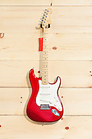 Fender Stratocaster red and white guitar on wood grain wall