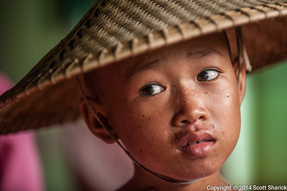 A young nun at a nunnery near Mandalay, Myanmar looks out from under her conical hat.