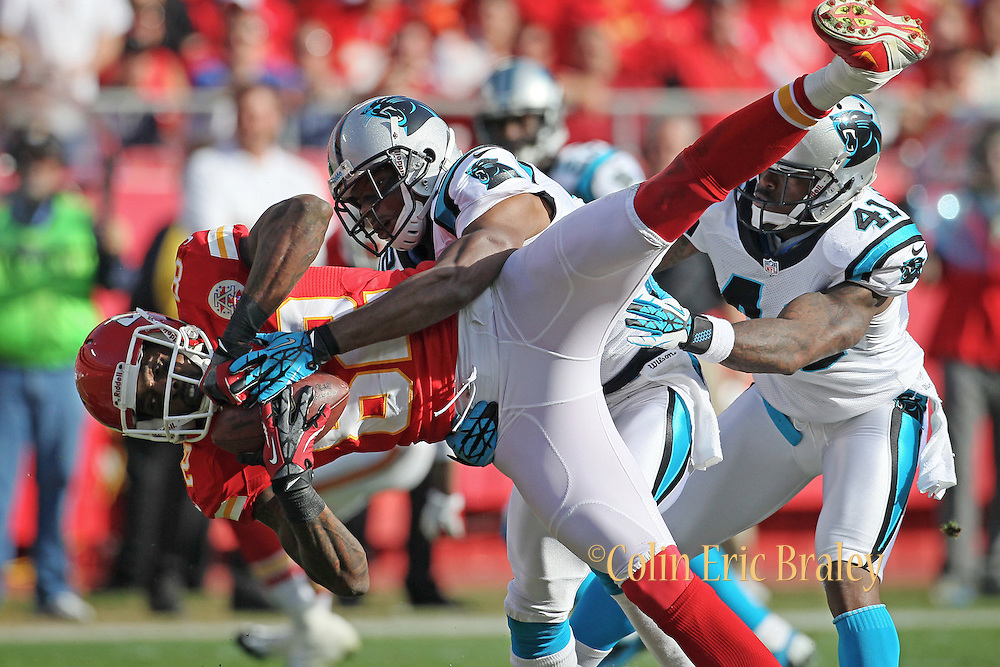Kansas City Chiefs wide receiver, Dwayne Bowe, (82) is stopped by Carolina Panthers cornerback, Josh Thomas, (22) as Panthers' cornerback, Captain Munnerlyn, (41) also defends during the first half of an NFL football game at Arrowhead Stadium in Kansas City, Mo., Sunday, Dec. 2, 2012. (AP Photo/Colin E. Braley)