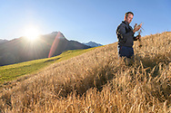 Roland Farrer in a field of barley (Hordeum vulgare), Parc Ela, Grisons, Switzerland