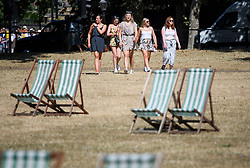 © Licensed to London News Pictures. 23/07/2018. London, UK. A group of young women walk past deck chairs in St James's Park central London, as the hot weather continues in the capital. Forecasters are predicting record temperatures this week. Photo credit: Ben Cawthra/LNP