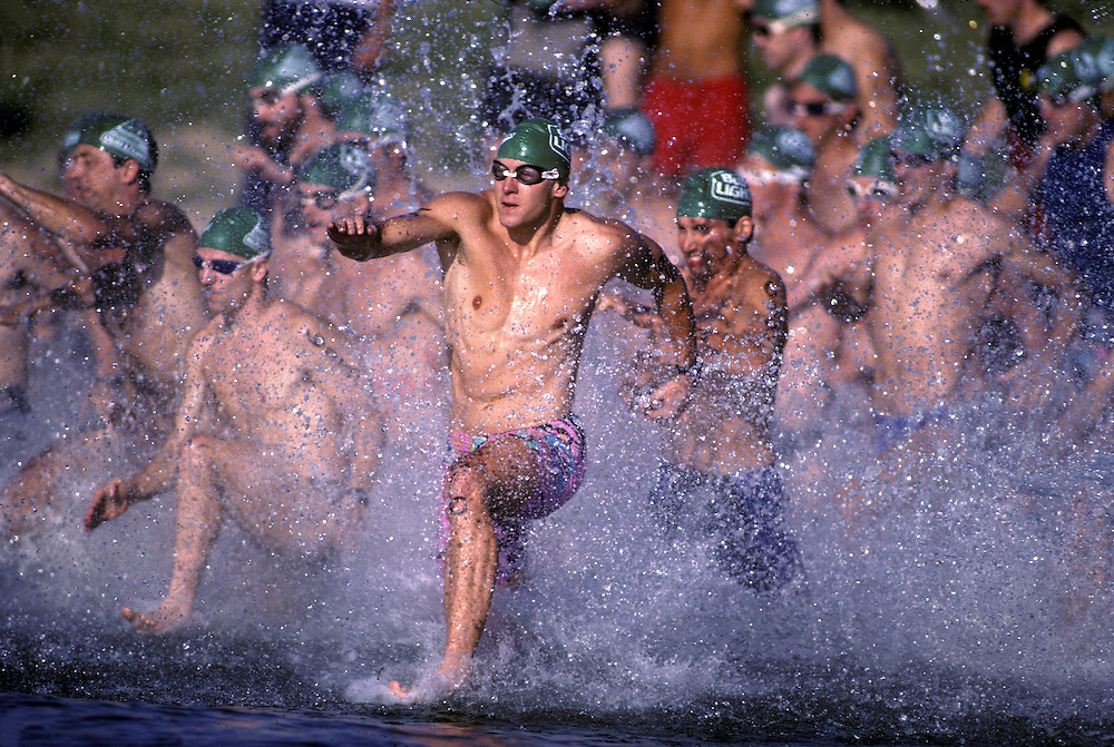 USA, Maryland, Triathlon racers sprint into water at start of men's swimming leg of race on summer morning