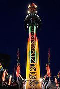 On the Hellevator, one of many rides at the Vancouver Pacific National Exhibition, riders are secured in seats, surrounding a 202-foot vertical tower, where the seat cart shoots upward at 75 kph and then free falls back towards the ground, providing an added free-falling force of negative 1 G on the way down.