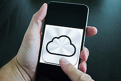 Apple iCloud online cloud storage logo on screen of iPhone 6 Plus smart phone