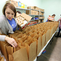 Jamie Ramels, a Junior Auxiliary of Tupelo member, fills bags with apple sauce snack packs as part of the Junior Auxiliary's Silent Servings program on Friday morning in Tupelo. The Silent Servings bags are for area students lacking nutritional support at home and are packed every two weeks then picked up by a school employee and also delivered to the schools by a Junior Auxiliary member. The program allows the students to have snack over the weekend that they may otherwise not get.