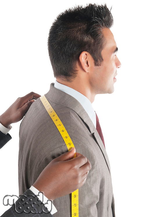 Tailor measuring across upper back from shoulder to shoulder of customer