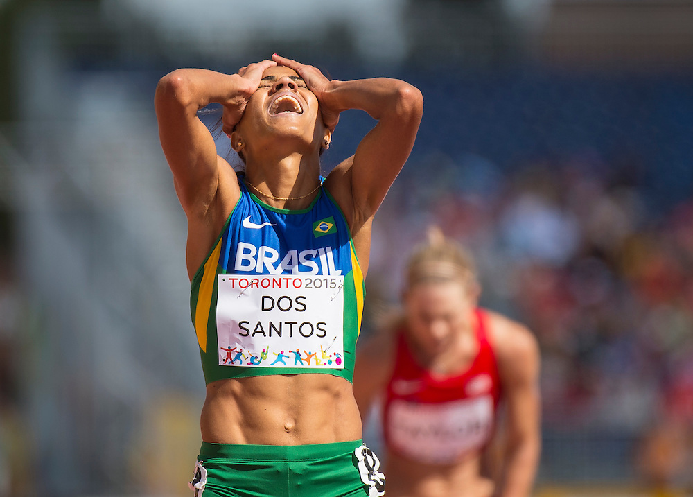 Juliana Paula Dos Santos, of Brazil, celebrates her gold medal finish in the women's 5000 meter race in athletics competition at the 2015 PanAm Games in Toronto.