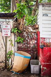 Trash piled between two houses in the Garden Street neighborhood.  Residents and volunteers gather for the Garden Street neighborhood cleanup and block Party hosted by E's Garden and Things, Long Path/Garden Street Community Association, and the Economic Development Authority's Enterprise and Commerical Zone Commission.  St. Thomas, USVI.  5 September 2015.  © Aisha-Zakiya Boyd