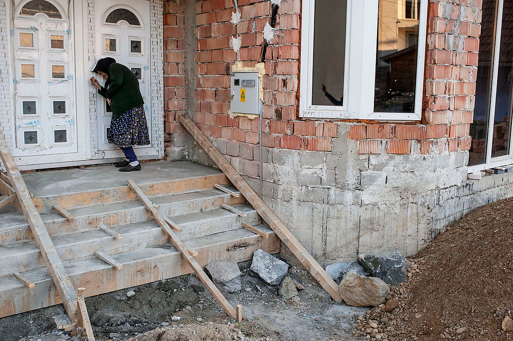 Maria Gherman struggles to open the door on the newly built home of her grandson who is working in France and building a new home for his family in the village.