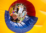 Luke Sorrels attempts to climb through a hole in an inflatable obstacle race during the Sugar Hill 75th Anniversary event on Saturday in Sugar Hill. (Staff Photo: David Welker)