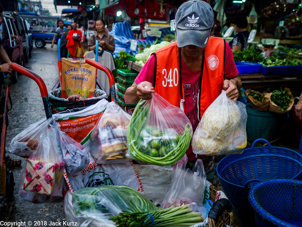"""04 DECEMBER 2018 - BANGKOK, THAILAND:  A porter packs up a customer's produce purchase, packaged in single use plastic bags. The issue of plastic waste became a public one in early June when a whale in Thai waters died after ingesting 18 pounds of plastic. In a recent report, Ocean Conservancy claimed that Thailand, China, Indonesia, the Philippines, and Vietnam were responsible for as much as 60 percent of the plastic waste in the world's oceans. Khlong Toey (also called Khlong Toei) Market is one of the largest """"wet markets"""" in Thailand. December 4 was supposed to be a plastic free day in Bangkok but many market venders continued to use plastic.    PHOTO BY JACK KURTZ"""