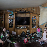 (L-R) Diana Nayokpuk, Hillary Sinnok, and Asta Nayokpuk at home in Shishmaref, Alaska, an Inupiat community of about 600 people near the Bering Strait. Shishmaref is one of at least 31 Alaska Native villages under imminent threat due to climate change, according to a 2009 report from the Government Accountability Office. Shishmaref is steadily disappearing because of erosion and flooding due to climate change. Only one quarter mile wide and two and half miles long, Shishmaref has been  grappling with rising sea levels that have eroded more than 200 feet of the village, since 1969, according to a relocation study published in February. Climate change has resulted in a reduction in the sea ice which buffers Shishmaref from storm surges. At the same time, the permafrost that the village is built on has also begun to melt, making the shore even more vulnerable to erosion.
