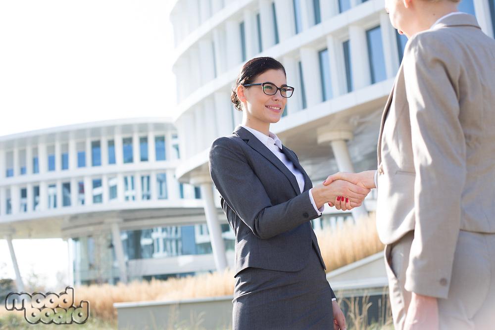Happy businesswomen shaking hands outside office building