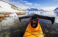 A Kayak guide demonstrates his unique balancing abilities with his Kayak while paddling in Danco Harbour.  The Antarctic Peninsula, Antarctica.  NO MODEL RELEASE