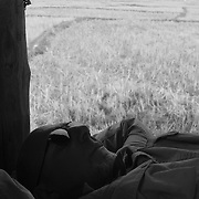 Billy Fritz, of Franklin, Pennsylvania, takes an afternoon nap in a small rice field bamboo hut near Gnommalath, during his motorbike tour of the Ho Chi Minh Trail in Laos. Fritz, a 60-year old orthopedic surgeon and commercial helicopter pilot, was a 1st lieutenant combat engineer company commander during the Vietnam War, serving in 1967-68.