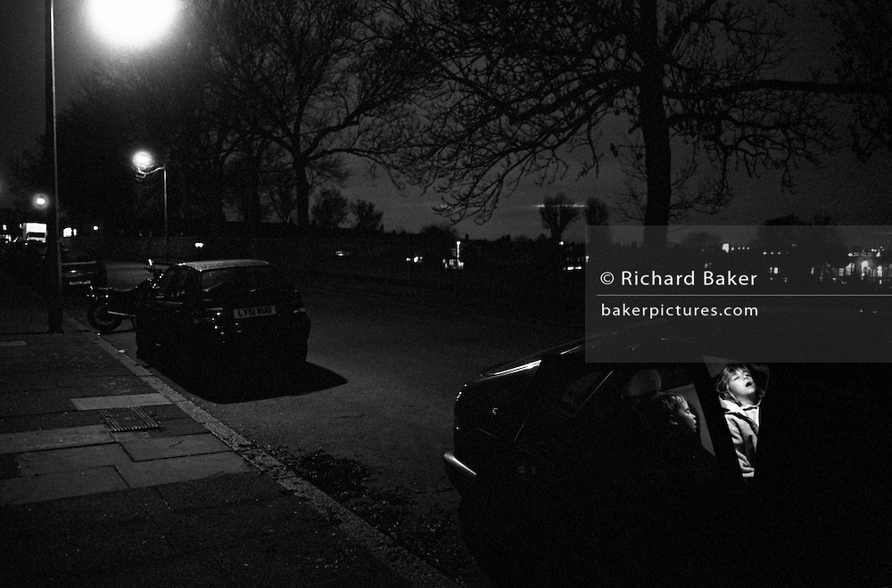"""Late at night in a South London street, two young children remain fast asleep in the back of their parents' car. It is a dark despite pools of light falling from street lighting that throw heavy shadows beneath other vehicles. The silhouettes of large ash trees can be seen against the city skyline. The interior lights in the car are switched on to reveal the sleeping childrens' faces. An older girl has her mouth wide open while her younger brother is seen in profile but both are peacefully unaware that they have arrived home after a long drive fro the countryside to the inner-city. From a personal documentary project entitled """"Next of Kin"""" about the photographer's two children's early years spent in parallel universes. Model released."""