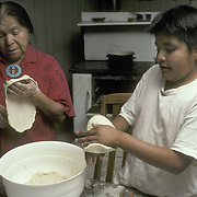 Grandson helps grandmother in kitchen, making fry bread, Zuni Pueblo, Zuni, NM<br />