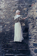 a lady in a white period dress is standing on old stone steps