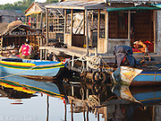 Floating Lives on the Tonle Sap - Woman feeding pigs while the man rests after fishing at dawn