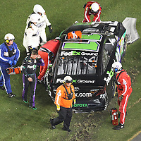 NASCAR Sprint Cup driver Denny Hamlin (11) climbs from his car after a wreck during the NASCAR Coke Zero 400 Sprint series auto race at the Daytona International Speedway on Saturday, July 6, 2013 in Daytona Beach, Florida.  (AP Photo/Alex Menendez)