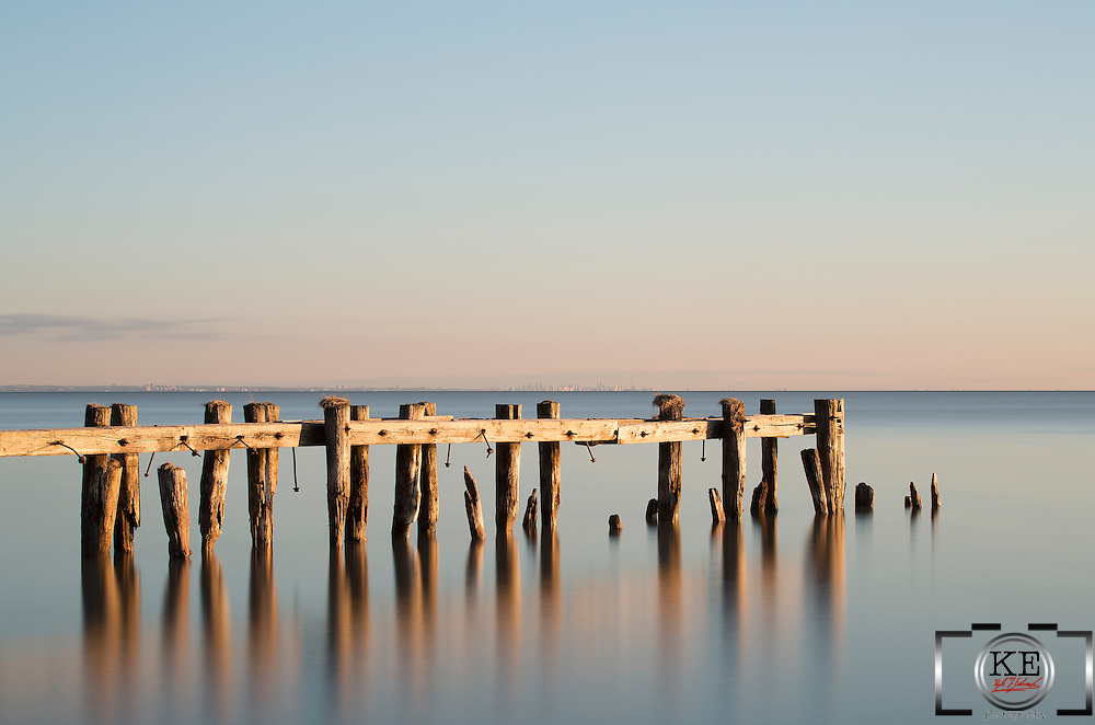 The remains of an old pier, reflecting the rays of the dawning sun and being reflected off of the still waters of the lake.
