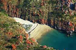 An aerial shot of one of many remote and isolated beaches on the Kimberley coast.  A tideline is clearly visible above the waterline.
