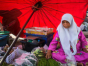 18 JUNE 2015 - PATTANI, PATTANI, THAILAND: A woman sells fresh vegetables from under a red umbrella in the market in Pattani. Many Thai Muslims go shopping early in the day to buy food for Iftar, the meal that breaks the day long Ramadan fast.    PHOTO BY JACK KURTZ