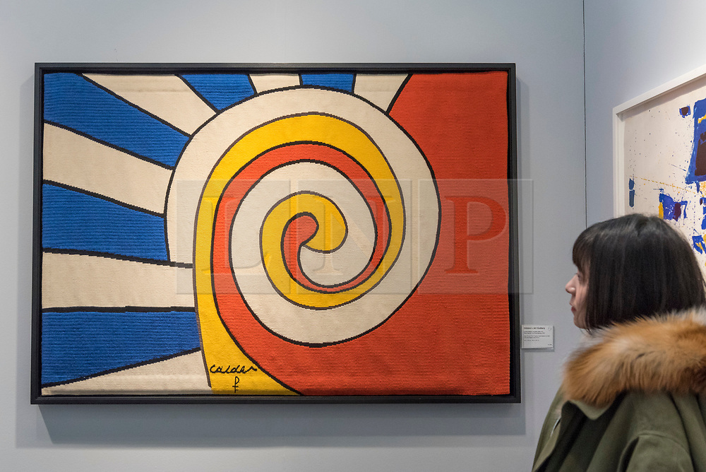 """© Licensed to London News Pictures. 16/01/2018. LONDON, UK. A visitor views """"Three Spirals"""" by Alexander Calder. Preview day of the 30th anniversary of the London Art Fair.  The fair launches the international art calendar with modern and contemporary art from leading galleries around the world and is taking place at the Business Design Centre, Islington from 17 to 21 January 2018.   Photo credit: Stephen Chung/LNP"""