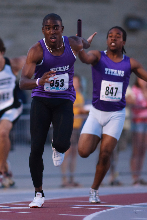 (London, Ontario}---09 June 2010) Kema Nnawuchi of Holy Trinity (Courtice) receives the baton from teammate Earl Anderson during the  at the 2010 OFSAA Ontario High School Track and Field Championships. Photograph copyright GEOFF ROBINS / Mundo Sport Images, 2010.