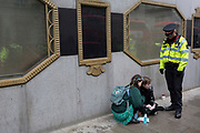 A police officer watches over an environmental protester with Superglue on her hands after glueing body parts to the road in Fleet Street on the 11th and final day of protests, road-blockages and arrests across London by the climate change campaign Extinction Rebellion, on 25th April 2019, in London, England.