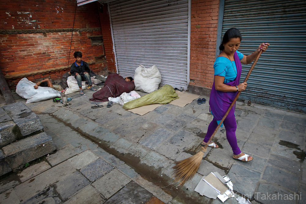 A woman sweeps the sidewalk as street children sleep in Kathmandu, Nepal on Aug 21, 2012..There are estimated around 5,000 street children working and living on the streets of Nepal and the number continues to grow with roughly 300 to 500 children leaving home every year. Some do so because of abusive, alcoholic parents, maltreatment at home, and the temptation to earn more money. They often end up taking drugs, abusing alcohol, and even suffering sexual abuse by locals and foreign tourists..(Photo by Kuni Takahashi)