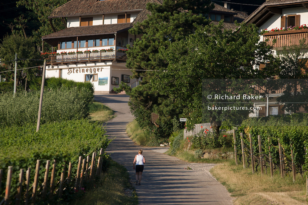 Woman walks uphill on a quiet, rural road in northern Italy, South Tyrol.