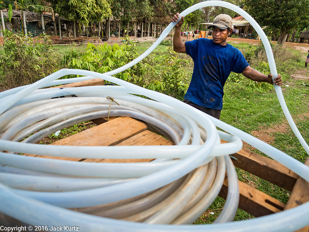 02 JUNE 2016 - SIEM REAP, CAMBODIA: NGOR, 33 years old, rolls up his hose after he sold water from his well to a family near his home east of Siem Reap. Cambodia is in the second year of  a record shattering drought, brought on by climate change and the El Niño weather pattern. Farmers in the area say this is driest they have ever seen their fields. They said they are planting because they have no choice but if they rainy season doesn't come, or if it's like last year's very short rainy season they will lose their crops. Many of the wells in the area have run dry and people are being forced to buy water to meet their domestic needs.      PHOTO BY JACK KURTZ
