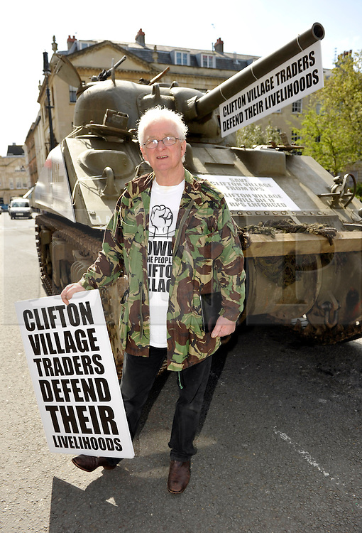 © Licensed to London News Pictures. 09/04/2014; Bristol, UK.  Tony Miles, (white hair and glasses) aka Smiley Miley from the Radio 1 Roadshow, rides in a WW2 Sherman tank through local streets in a protest by residents and traders from Clifton Village in Bristol about plans for a Residents Parking Scheme in their area from Bristol's elected Mayor, George Ferguson.  They say the business and social life of the area will be hit very hard by the RPS with customers and visitors unable to park, and that some businesses will have to close or move away from the area.  The tank is a symbol of defending their area against RPS.<br /> Photo credit: Simon Chapman/LNP