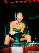 Girl on a dodgem sticking out her tongue with red blood/juice on her neck and chin, Ibiza, 1998