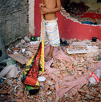 A boy holds a samba flag on destroyed bricks from a demolished home in Largo do Tanque, in Rio de Janeiro, Brazil, on Monday, Feb. 25, 2013. Homes were manually destroyed to render them uninhabitable.<br />