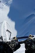 Craig Branch skis under the legs of Tony Harrington at Points North Heliskiing in Corova Alaska. MR