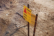 "Israel, Aravah, near the Jordanian border A mine field, a yellow warning sign in Hebrew Arabic and English ""Danger Mines"""
