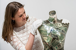 "© Licensed to London News Pictures. 08/06/2015. London, UK. A Sotheby's staff member looks at ""Venus aux dollars"" by Arman (est. £16,000-22000), at the preview of ""To the Bearer on Demand"", a private collection of 21 works inspired by the US dollar, including Andy Warhol masterpieces, which will be auctioned on 1 and 2 July.  The collection is estimated to realise £50 million. Photo credit : Stephen Chung/LNP"